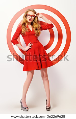 Gorgeous fashion model in red dress and elegant red glasses posing over red circles of the target. Beauty, fashion. Optics, eyewear. Full length portrait. - stock photo