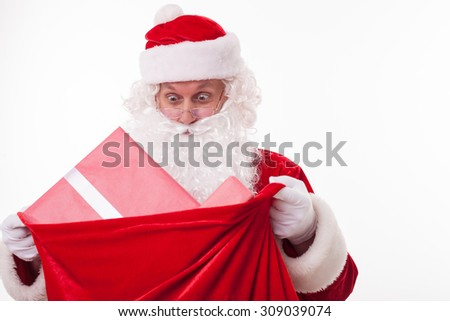 Gorgeous Father Christmas is holding a red sack of gifts. He is opening it and looking at big boxes with surprise. His eyes are wide open. Isolated and copy space in right side - stock photo