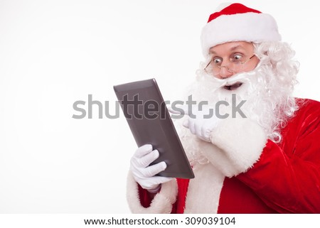 Gorgeous Father Christmas is using a laptop with pleasure. He is looking at it with surprise and laughing. Isolated on background and copy space in left side - stock photo