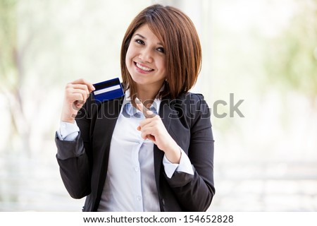 Gorgeous female Asian bank representative holding a credit card in one hand and pointing at it with the other - stock photo