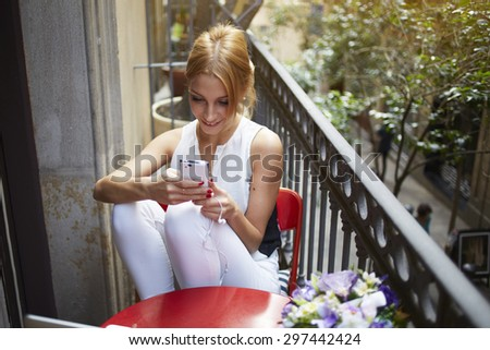 Gorgeous female enjoying recreation time while chatting with her mobile phone on terrace, smiling successful young woman read good news on the smart phone, student hold telephone looking at the screen - stock photo