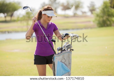 Gorgeous female golfer choosing a golf club for her next shot - stock photo