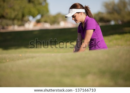 Gorgeous female golfer inside a trap focusing on her shot - stock photo