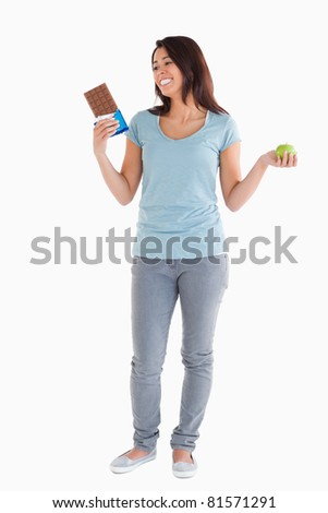 Gorgeous female holding a chocolate bar and an apple while standing against a white background