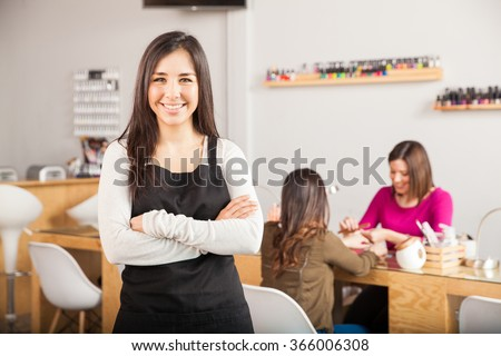 Gorgeous female Latin business owner standing in front of her nail salon while a customer gets a manicure - stock photo