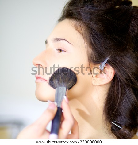 Gorgeous female model getting makeup