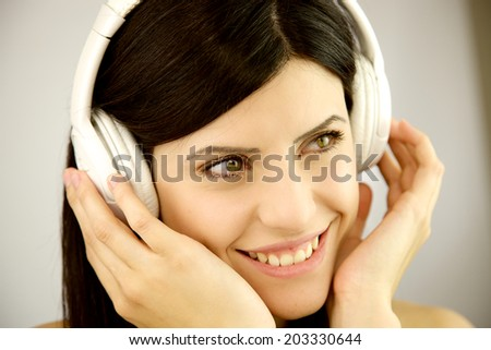Gorgeous female model happy listening music closeup - stock photo