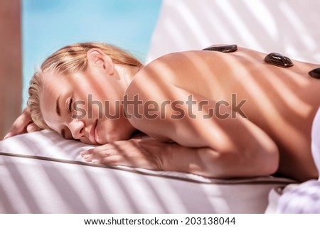 Gorgeous female spending summer vacation on luxury spa resort, massage procedure with black hot stones on the beach - stock photo