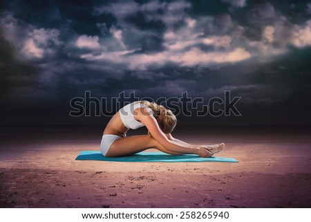 Gorgeous fit blonde in seated forward bend pose against dark cloudy sky - stock photo