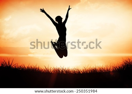 Gorgeous fit blonde jumping with arms out against orange sunrise - stock photo