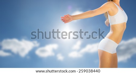 Gorgeous fit blonde standing with arms out against cloudy sky with sunshine - stock photo