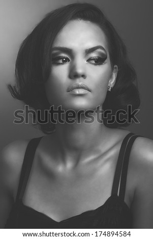 Gorgeous girl portrait with a professional makeup, pink lips and frightening look. Black and white version. - stock photo