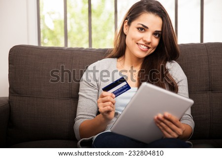 Gorgeous girl using her tablet computer and credit card to buy some stuff online - stock photo