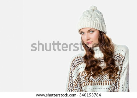 Gorgeous girl wearing warm knitted christmas jumper and a hat, xmas concept on white background