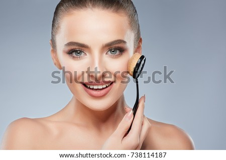 Gorgeous girl with brown hair fixed behind, clean fresh skin, big eyes and naked shoulders posing at gray studio background, beauty photo, holding make up brush and smiling.