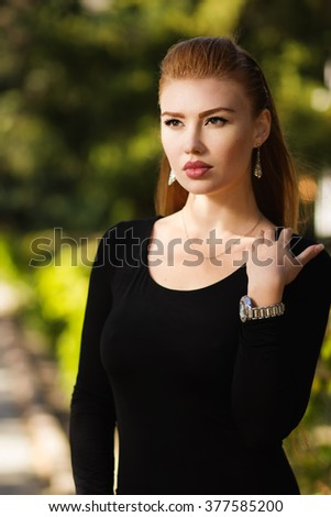 Gorgeous girl with puffy lips natural. Portrait of beautiful sexy urban girl walking in city park. Portrait of a young gorgeous redhead girl in black clothing - stock photo