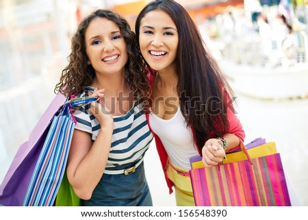 Gorgeous girlfriends with paperbags looking at camera in trade center - stock photo