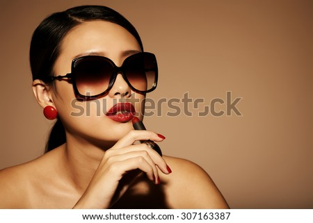 Gorgeous glamorous woman in sunglasses applying red lipstick