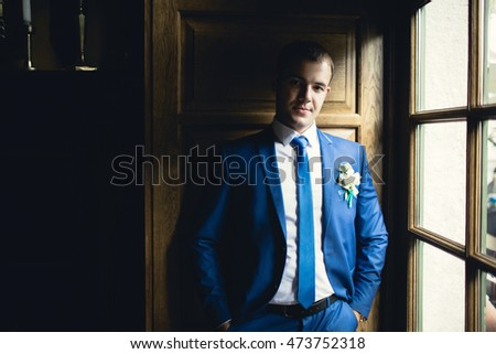 gorgeous groom  standing at the window
