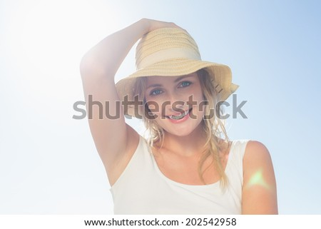 Gorgeous happy blonde posing at the beach on a sunny day - stock photo