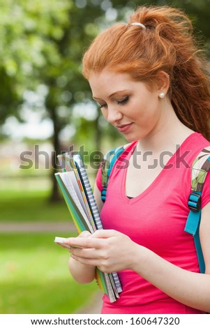 Gorgeous happy student holding notebooks texting on campus at college - stock photo