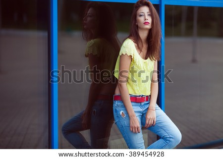 Gorgeous hipster girl in blue jeans in the summer city. Modern youth lifestyle concept. Copy-space. Outdoor shot - stock photo