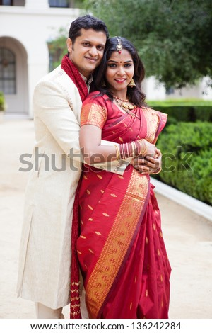 Gorgeous Indian bride and groom looking at camera - stock photo