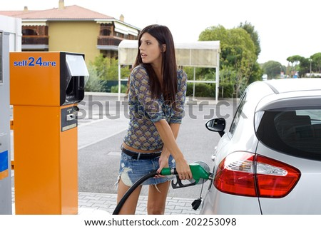 Gorgeous italian lady filling car with green gas - stock photo