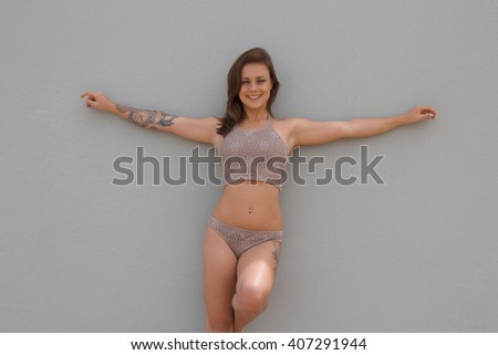 Gorgeous lady with tattoos in bikini with blank background - stock photo