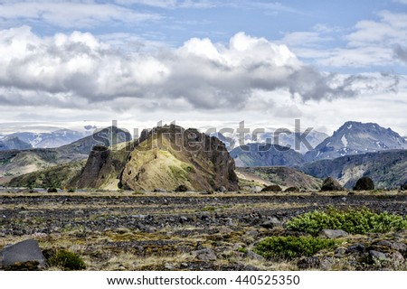 Gorgeous landscape view of lava rock fields with volcanic mountains and glaciers in the distance in Iceland. - stock photo