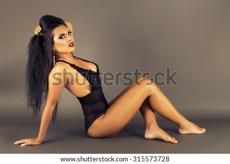 Gorgeous latin young woman lying on the floor over gray background, studio shot - stock photo