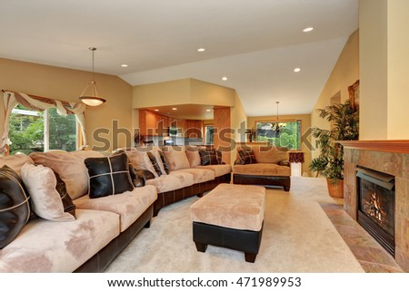 Gorgeous living room interior with beige velvet and leather sofa set and fireplace . Kitchen room view. Northwest, USA