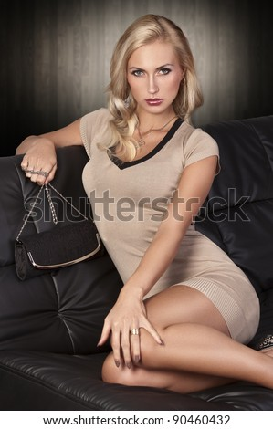 gorgeous long haired blonde posing on a black leather sofa wearing a mini dress and holding a black purse - stock photo