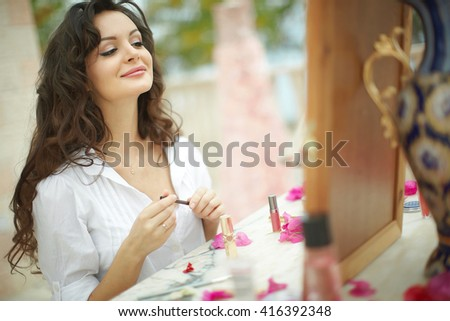 Gorgeous, lovely bride, model preparing to wedding day using lipstick. Dream wedding with lot of flowers, shiny and ethereal.