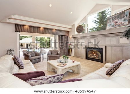 Gorgeous luxury furnished family room interior with vaulted ceiling. Decorated with palm tree in a pot and candles by the window. Northwest, USA