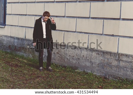 Gorgeous man in a raincoat standing in front of a brick wall. Blond. With a cigarette. Oldshool 70s colour graded.