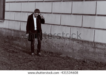 Gorgeous man in a raincoat standing in front of a brick wall. Blond. With a cigarette. Vintage Black and White colour graded.