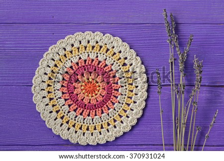 Gorgeous Mandala Crochet Doily and Lavender Flowers  on Purple Rustic Wooden Background