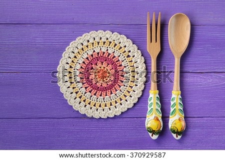 Gorgeous Mandala Crochet Doily and spoon with fork for salads on Purple Rustic Wooden Background