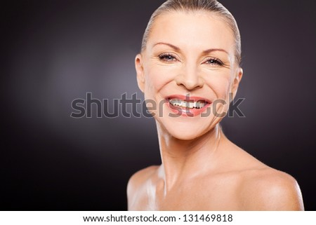 gorgeous mid age woman smiling against black background - stock photo