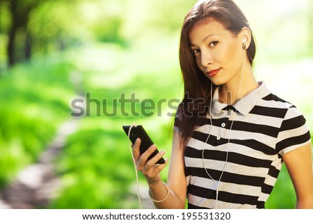 Gorgeous mixed race model in trendy casual shirt listening to music and texting message on smartphone app walking in park with green grass. Sunny summer weather. Copy-space. Close up. Outdoor shot - stock photo