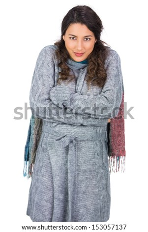 Gorgeous model with winter clothes being cold while posing on white background
