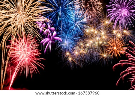 Gorgeous multi-colored fireworks display on black background, with copyspace - stock photo