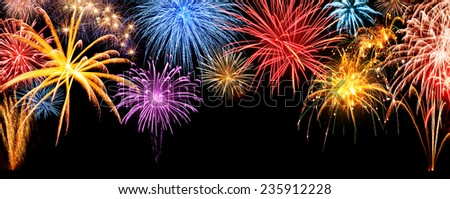 Gorgeous multi-colored fireworks display on black night sky, with freely extendable copyspace - stock photo