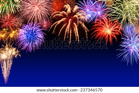 Gorgeous multi-colored fireworks display on dark blue night sky, with copyspace - stock photo