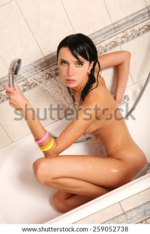 Gorgeous nude female in shower. Beautiful woman bathing - stock photo