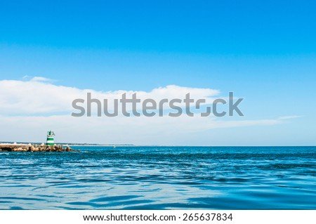 gorgeous ocean view of a small lighthouse in Tavira Island, Portugal. - stock photo