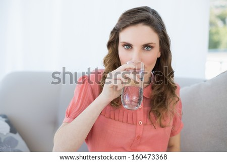 Gorgeous pregnant woman drinking glass of water sitting in living room looking at camera - stock photo