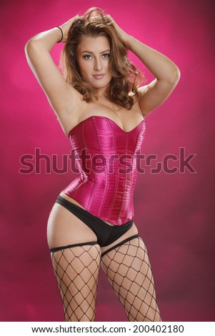 Gorgeous red-hair in sexy fishnet stockings on magenta - stock photo