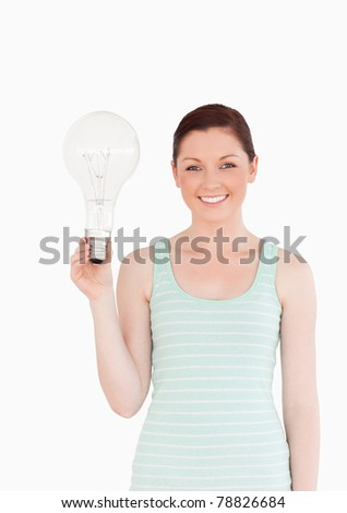 Gorgeous red-haired female holding a bulb while standing on a white background
